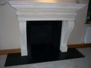 Large limestone fireplace mantel installation in Surrey
