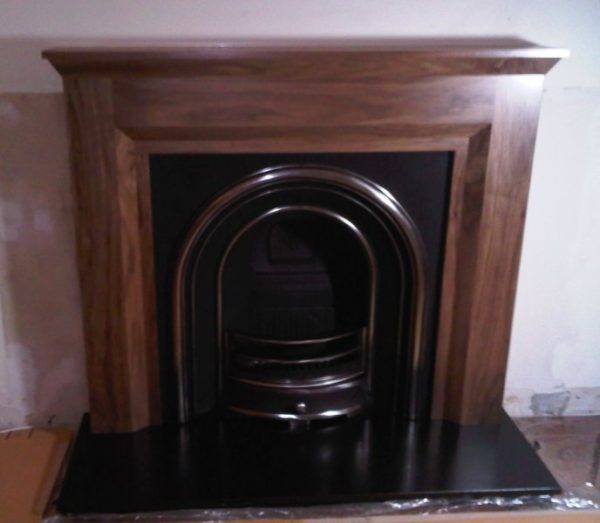 Simple walnut fire surround and cast iron fireplace