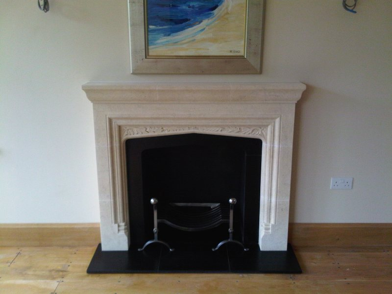 Stone ornate fireplace surround and fire dogs