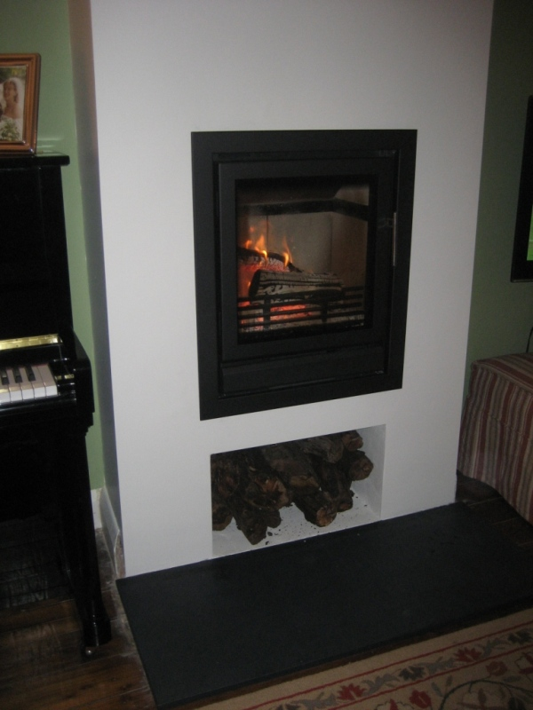 contemporary wood burning stove with log storage shelf