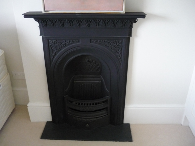 Small black cast iron fireplace surround in a bedroom