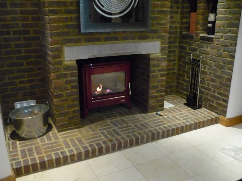 Red wood burner stove in brick surround