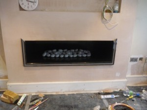 Black Granite Hole in the Wall Fireplace with pebbles