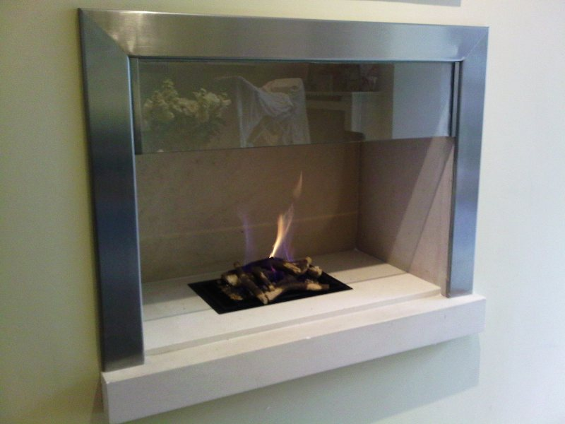 Polished steel contemporary fireplace surround in a living room with gas fire