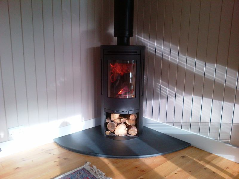 Corner wood burning stove with log storage