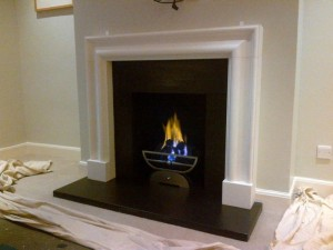 Limestone bolection fireplace with Morris basket and gas fire