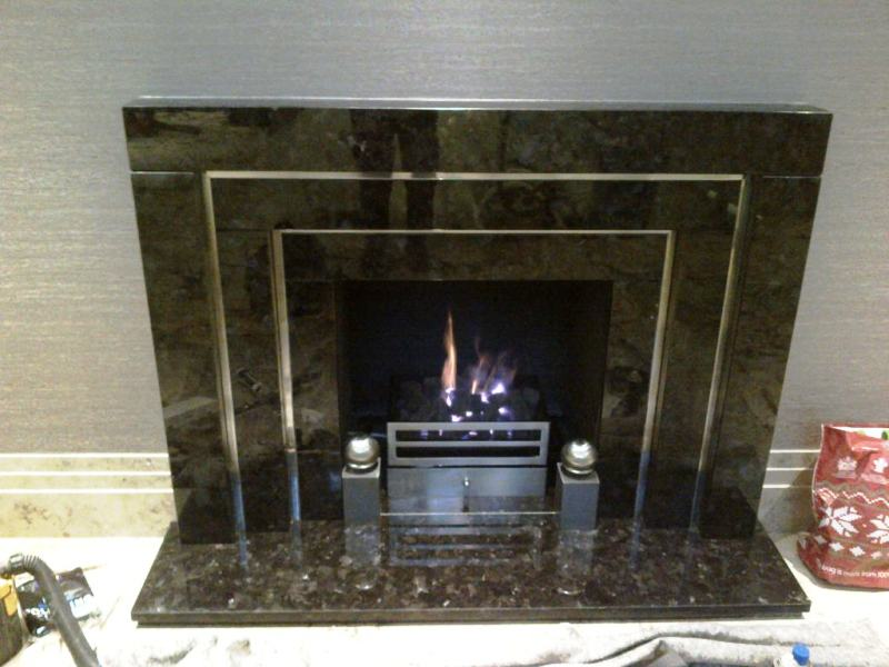 Black marble fireplace with chrome inlay and steel fire basket