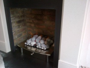 Flat Victorian limestone fireplace with large Zen basket with pebbles