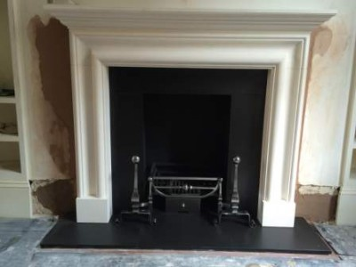 limestone bolection fireplace with Chesneys Morris basket and Burton firedogss