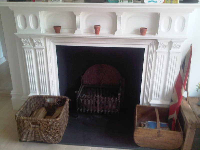 White painted wooden fireplace mantle surround with log basket