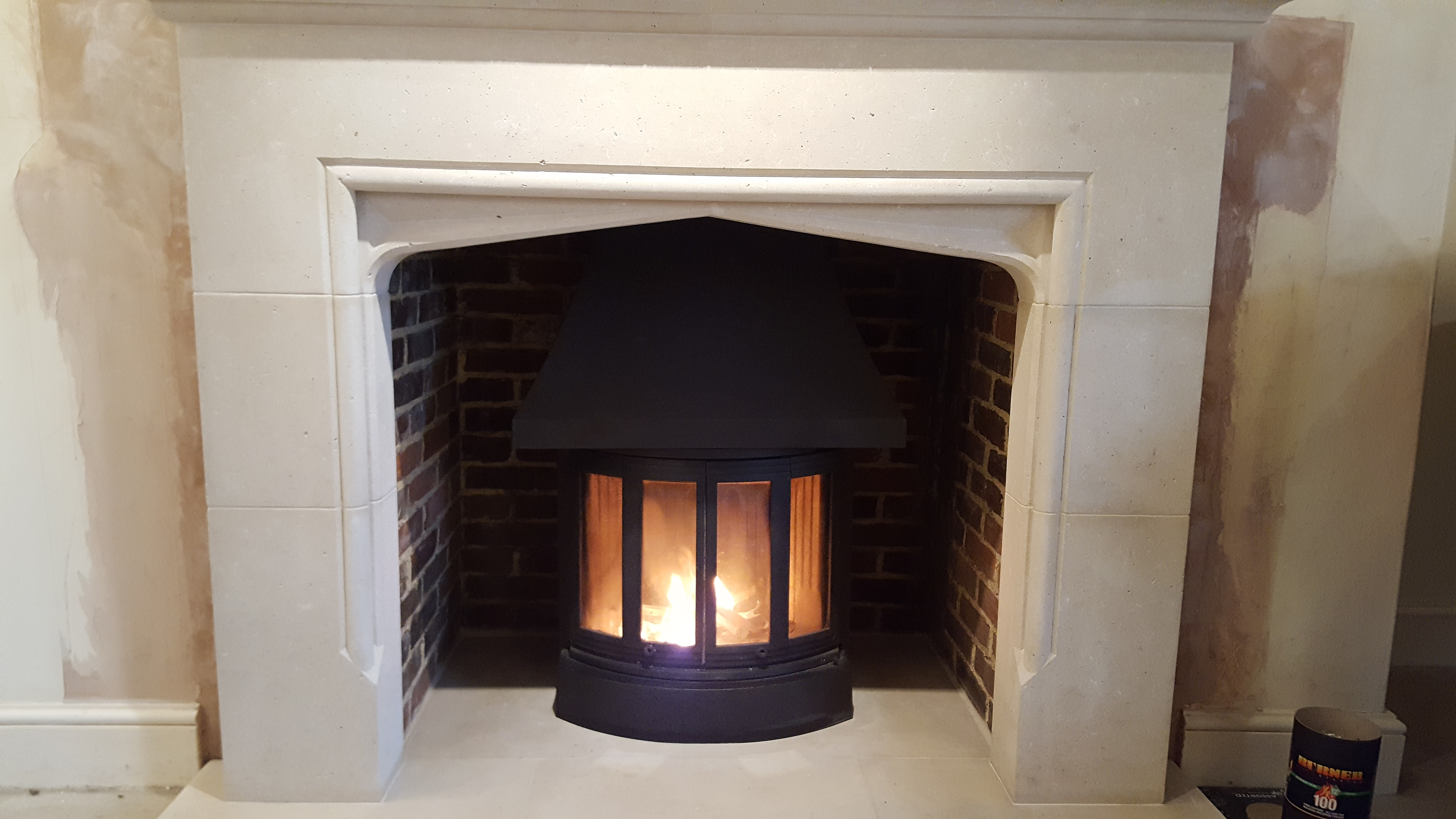 Jotul wood burning stove with limestone fireplace surround